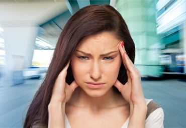 Woman with headache in front of blurry surroundings