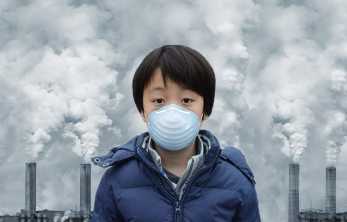 Boy wearing mouth mask surrounded by air pollution
