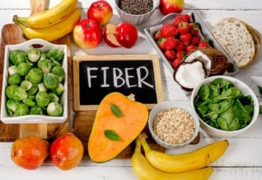 """Fiber"" sign on table surrounded by fruits, vegetables, and grains high in fiber"