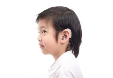 young Asian boy with hearing device in ear
