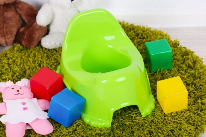 potty chair on a rug surrounded by children's toys