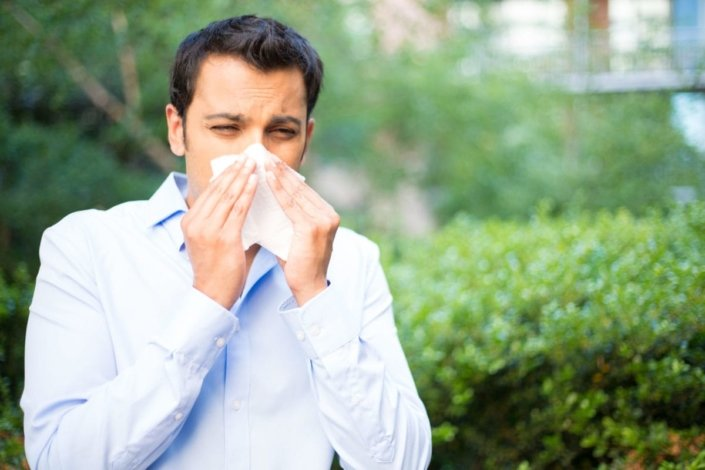 man with allergies outside blowing his nose, allergic to trees in background