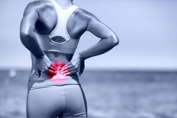 Athletic woman standing outside, rubbing lower back muscles