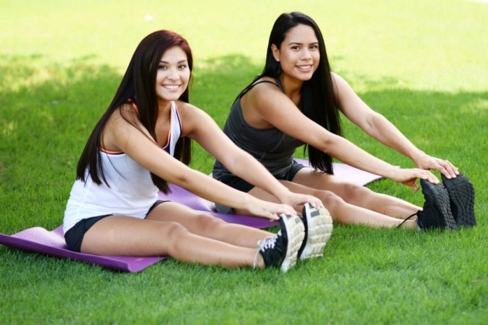 Two women sitting in grass stretching before exercising