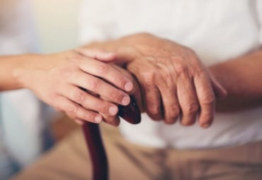 close-up of an elderly man's hands on top of a cane with a caregiver's hand on top
