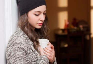 sad-looking young woman looks down over a mug of hot beverage