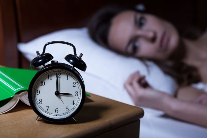 woman lying in bed stares at clock in the middle of the night
