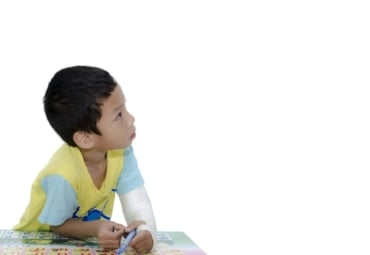 boy leaning over table and looking off into distance