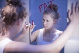 "A thin, young woman looking in the mirror and writing the word ""Fat"" in red lipstick"