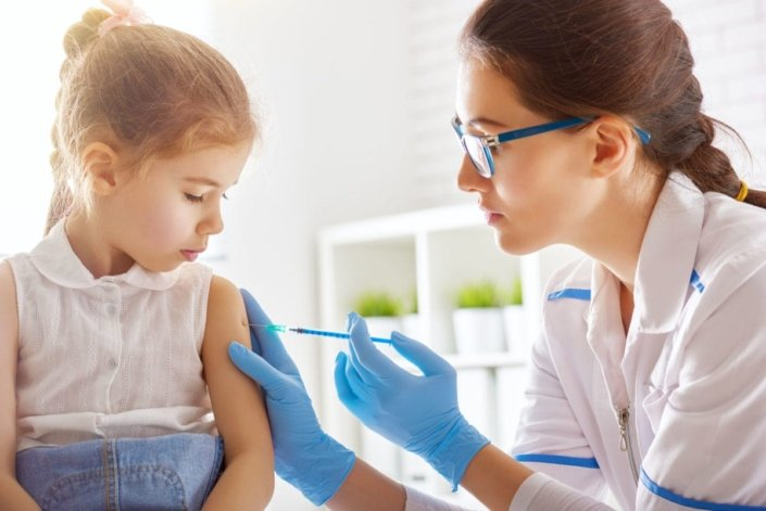 doctor gives a vaccination to a young girl