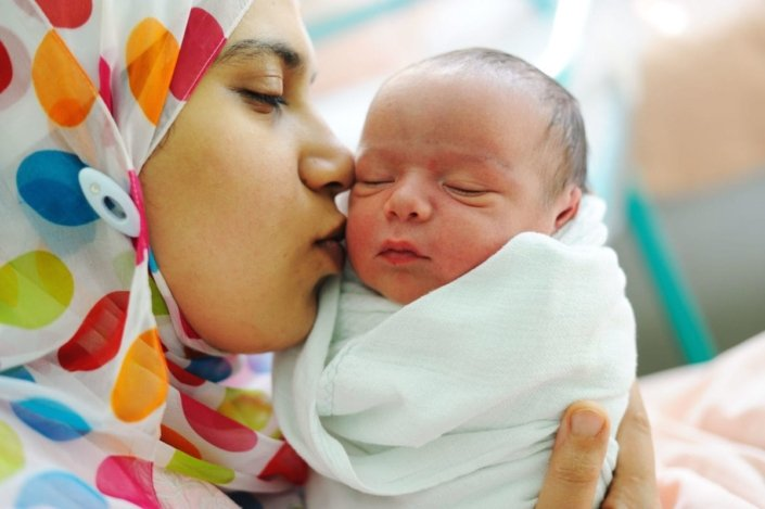 mother holds and kisses her newborn baby