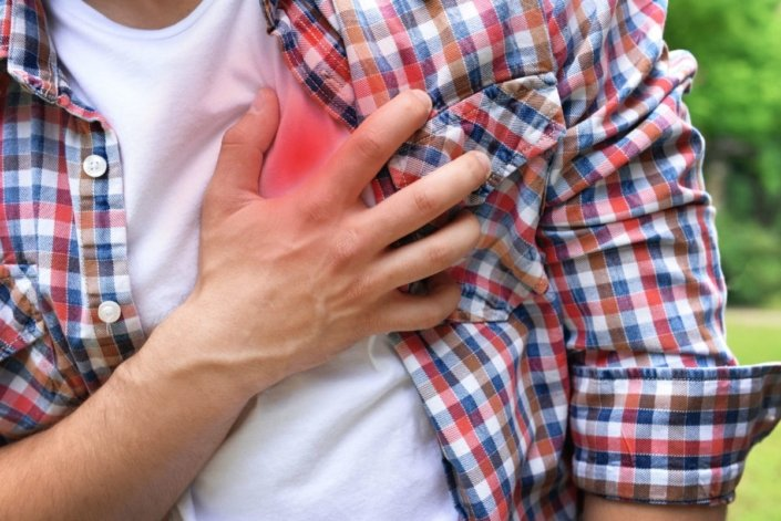 Man holding chest in pain