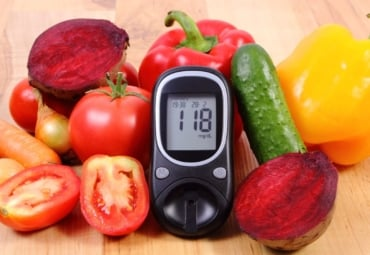 A glucose meter propped up among a tabletop of fruit and vegetables