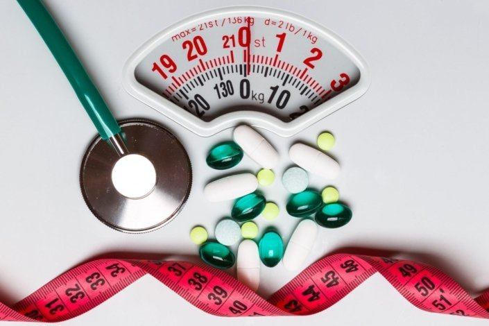 stethoscope, measuring tape, and pills sitting on a scale