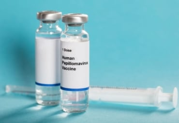 Bottle of HPV vaccine sitting next to syringe