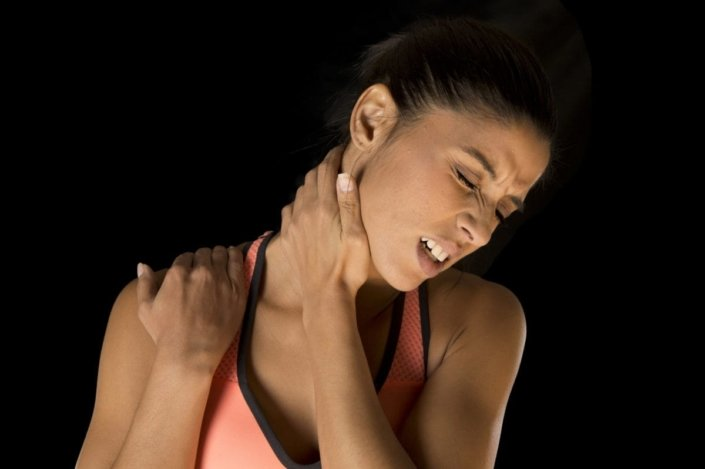 a young athletic woman grips her neck and shoulder and grimaces in pain
