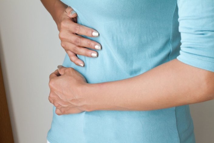 Woman with gallstones holds her stomach in pain
