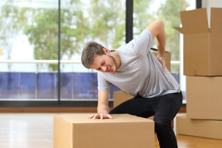 Man suffering from backache while moving boxes