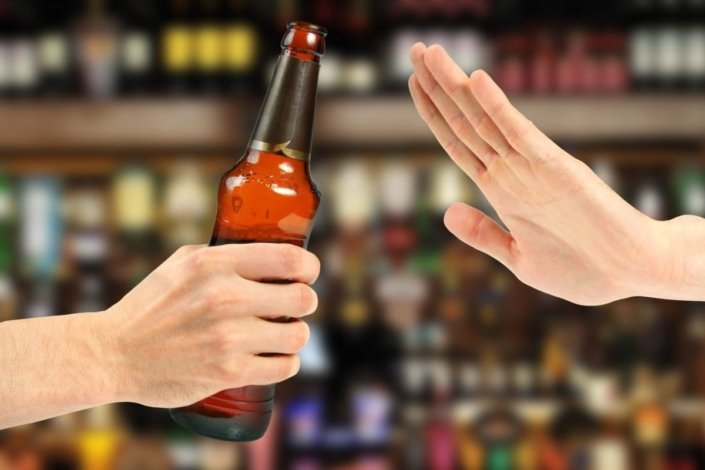 hand rejects a bottle of beer in a bar