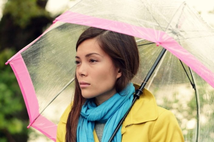 sad-looking woman in a coat and scarf stands under an umbrella in the rain