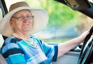smiling senior woman in glasses driving automobile