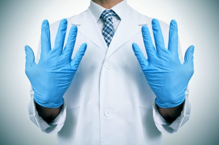 A doctor wearing blue latex gloves