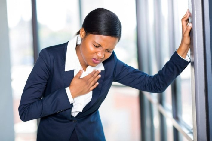 young African American businesswoman having chest pain