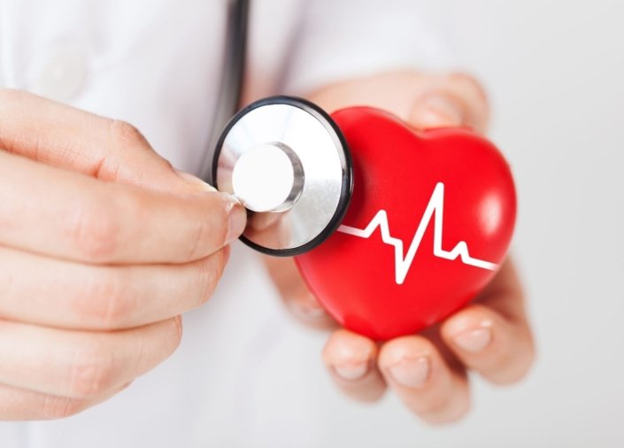 A doctor holding a stethoscope up to a toy heart