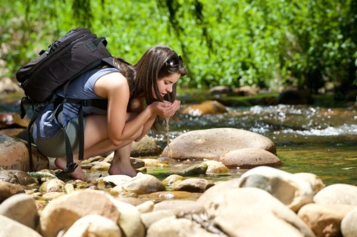 Young woman drinking from stream