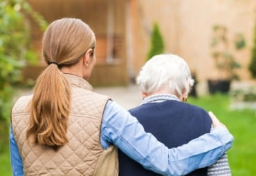 a female caregiver puts her arm around an elderly woman as they walk outside