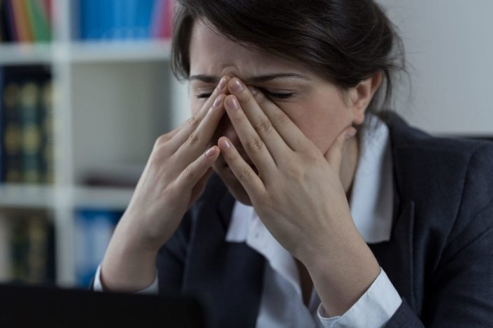 Woman in business clothes holding sinuses in pain