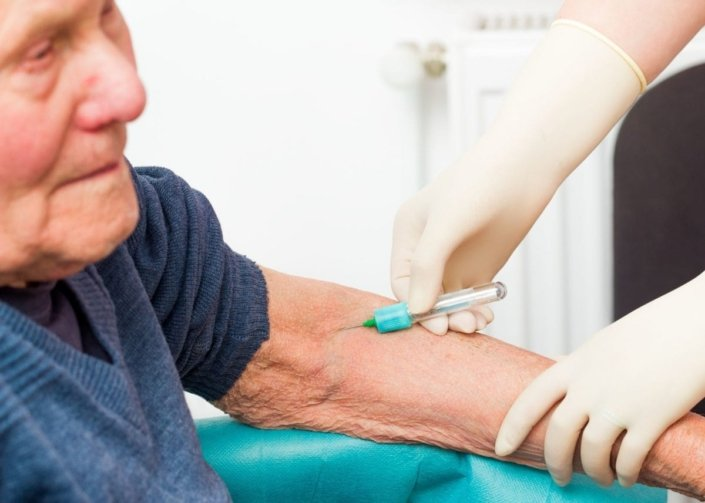 senior man receives injection from medical worker with gloved hands
