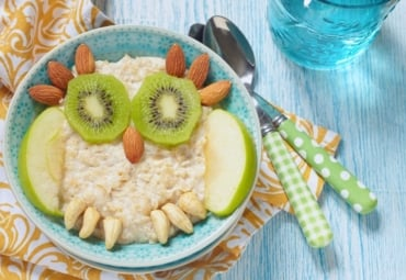 kids breakfast of oatmeal layered with fruit and nuts so it looks like an owl