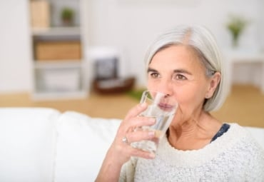 Middle-aged woman drinking a glass of water in the living room and looking into the distance
