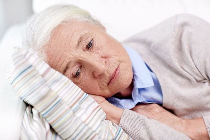Elderly, depressed woman lying on pillow