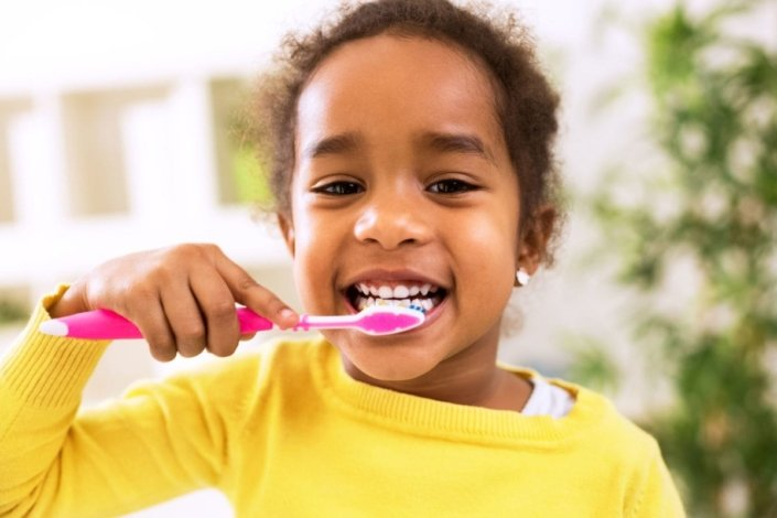 Little Girl Brushing Her Teeth And Smiling