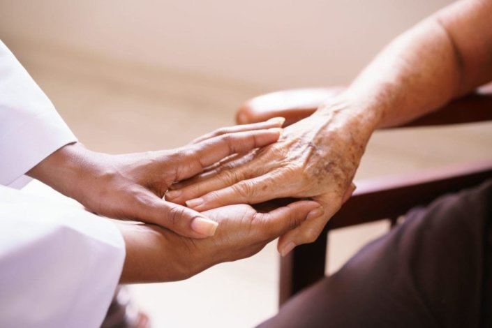 Touching hands of ill patient in hospice care and doctor providing care