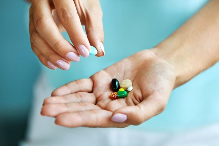 closeup of female hand holding variety of colorful pills on palm