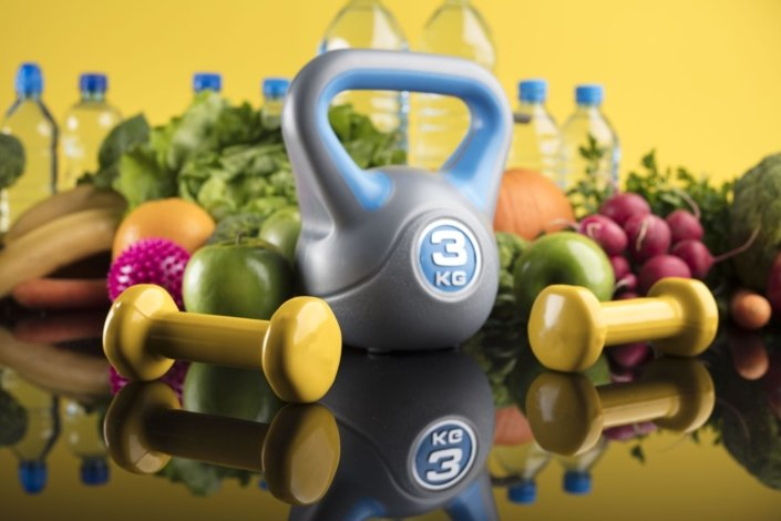 hand weights, water bottles and fresh fruit and vegetables