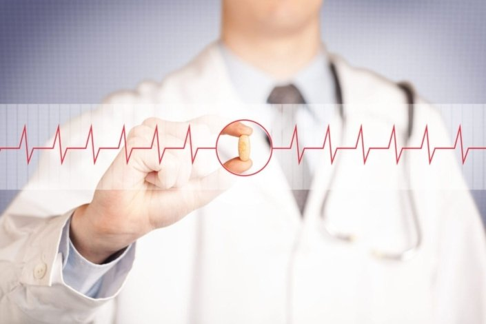 close-up of a doctor holding a pill, focused on a heartbeat graph