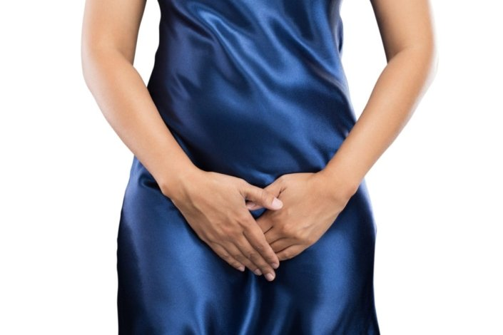 Woman with bacterial vaginosis dressed in blue silk nightgown with hands covering her crotch and lower abdomen