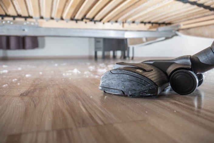 a vacuum sucks up dust on a hardwood floor under a bed