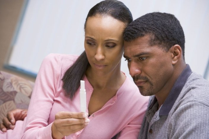 Couple looking disappointed at negative home pregnancy test