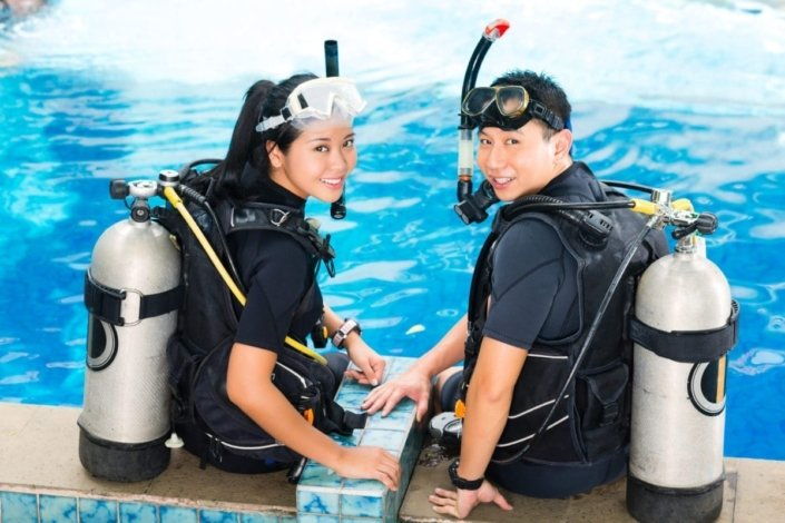 Woman and man in wet suits with oxygen tanks, learning how to safely scuba dive