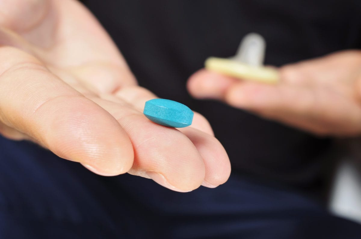 Man holding condom in one hand and blue pill in the other