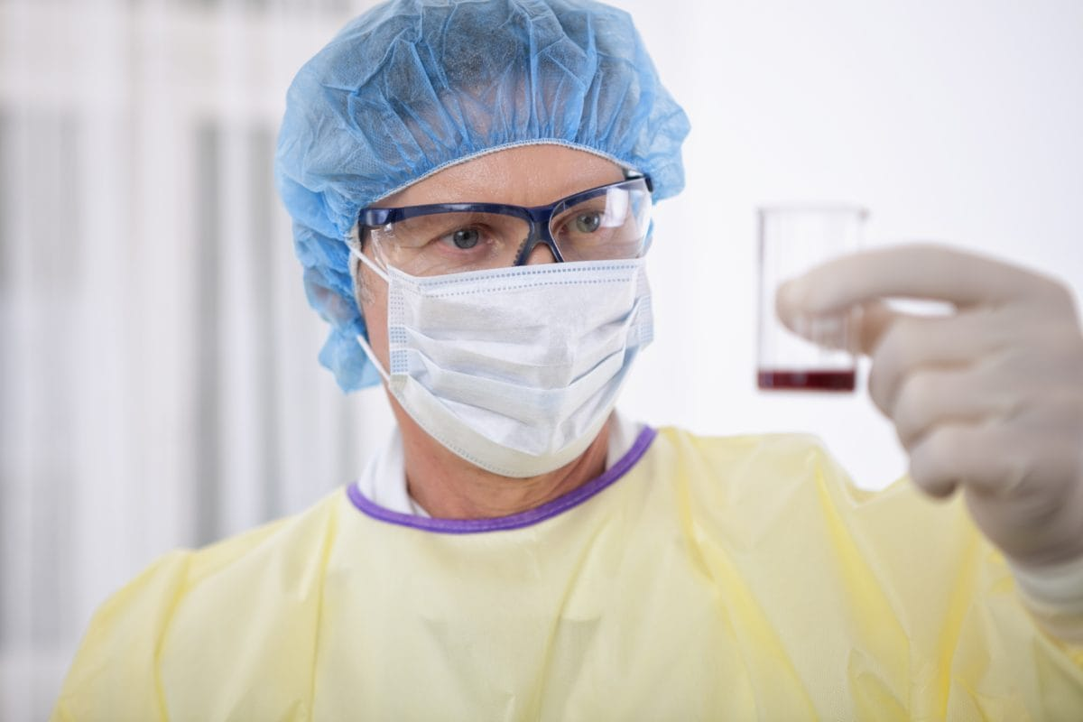Scientist or doctor wearing protective gear while handling blood in a lab or hospital