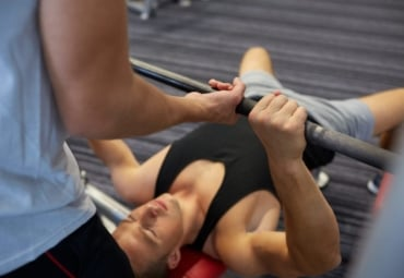 A man bench-pressing weights with another man spotting him