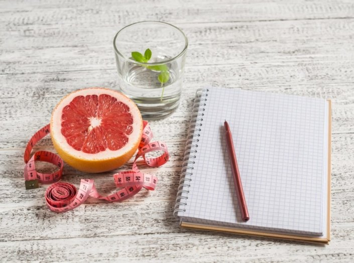 Open food diary next to a grapefruit, glass of water, and measuring tape