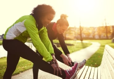 Two young women doing leg safety stretches before running in park