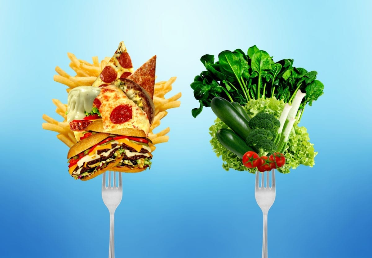 Choosing between a fork with greasy, cholesterol-rich food or a fork with fresh, healthy vegetables and fruits.